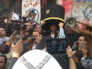 Bassem Yousef wearing Morsi's PhD award hat while going to court