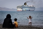 Arriving in Greece,  a child plays on the beach unaware of his plight