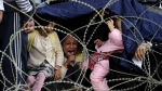 Little girl cries trying to hide from the rain on the Greece-Macedonia border