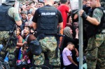 Greece-Macedonia border: police standing above refugees